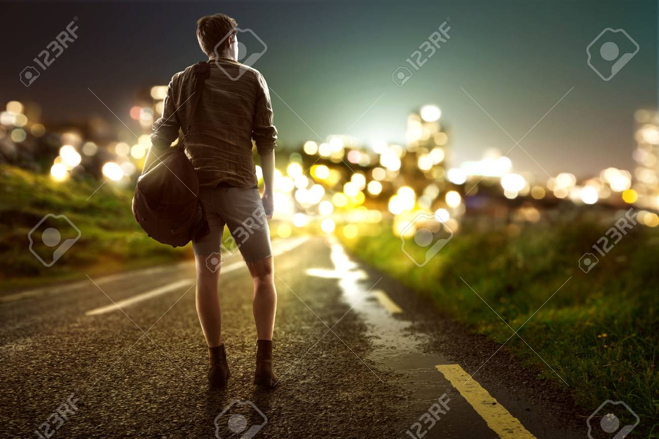 Guy walks towards city lights on a country road - 77028599