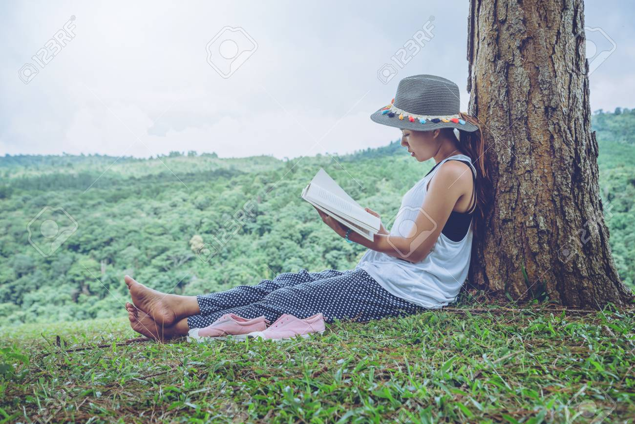 Asian women relax in the holiday. Sit read books on grassland in the park. - 91532298