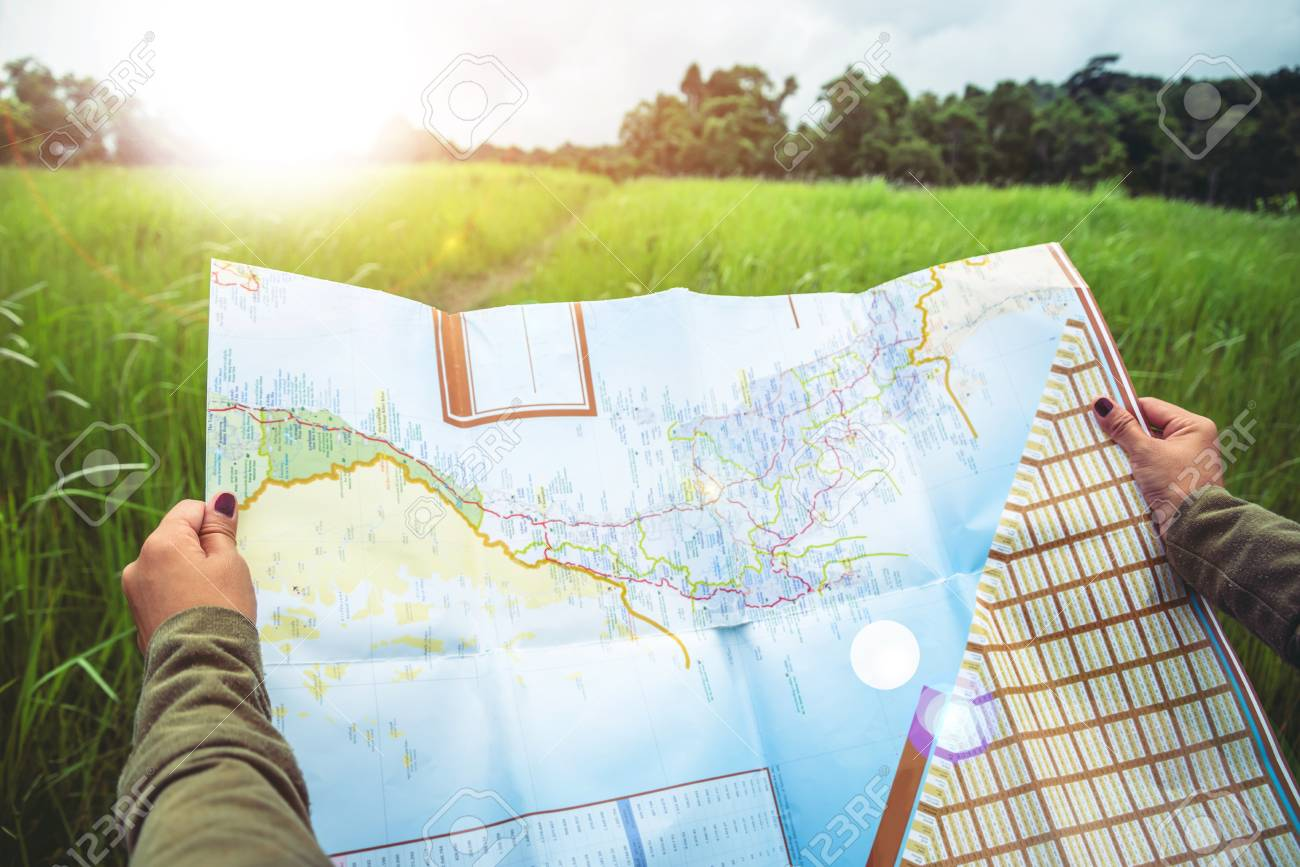woman travel. Asian women's hand catches a map of travelNatural forest on the grassland - 91814446