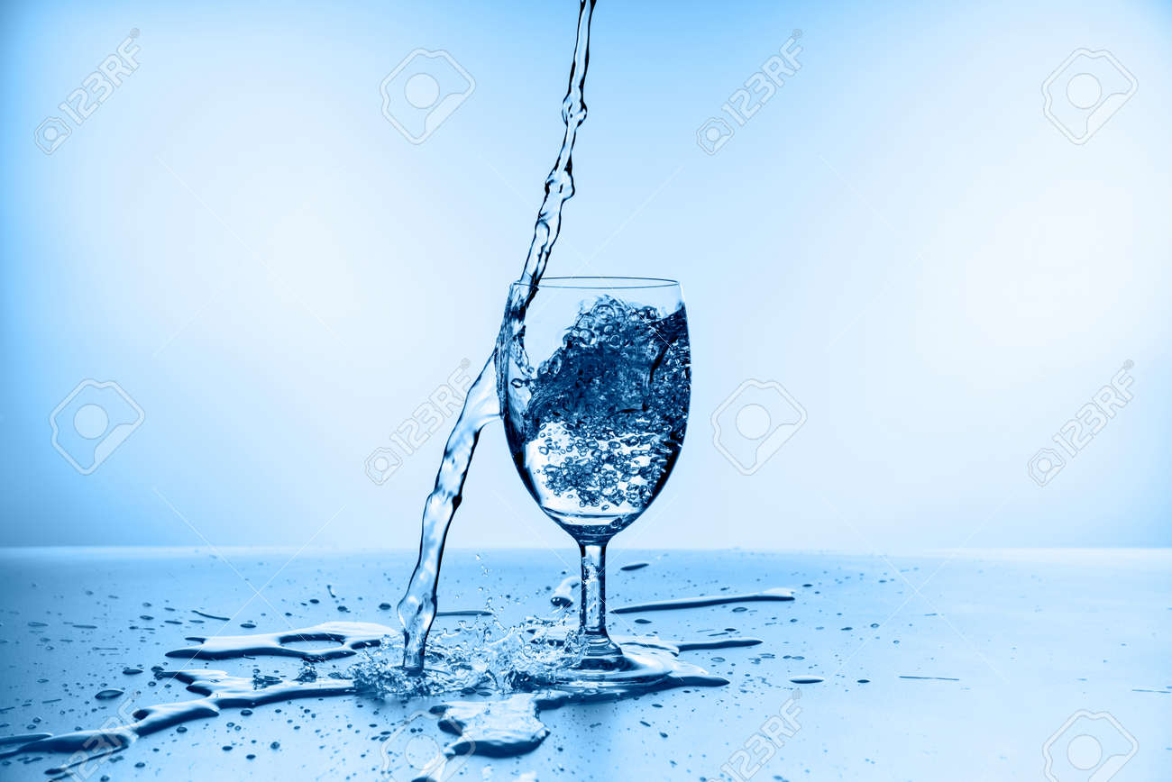 water splashing from glass isolated on blue background - 155035637