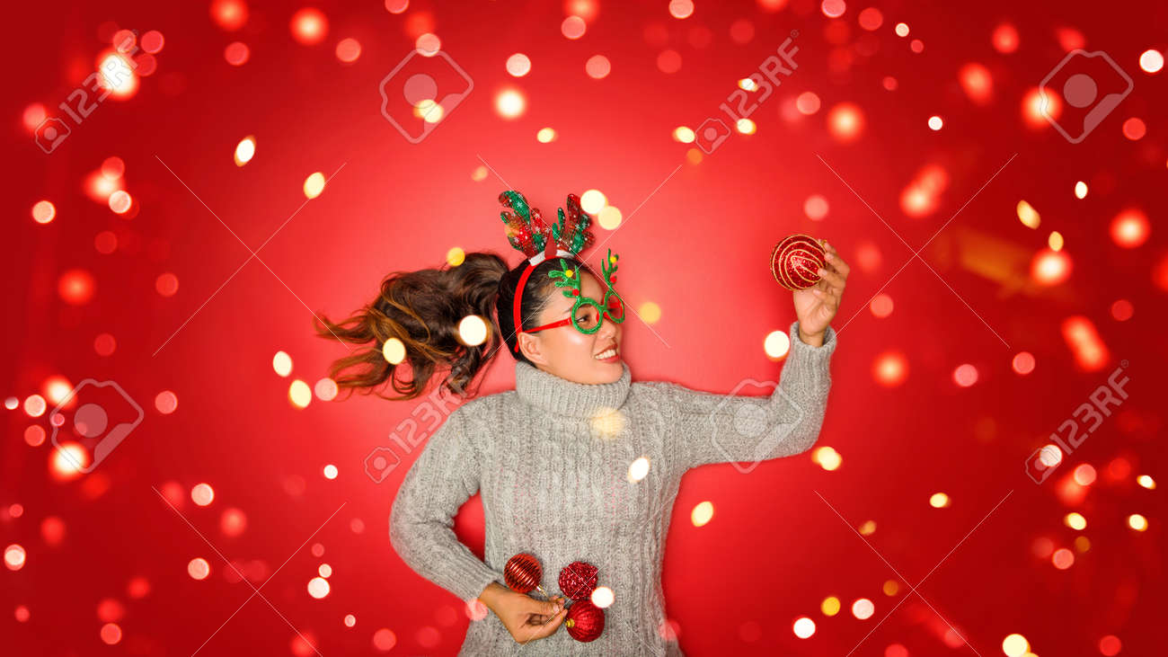 The girl is using the hand to hold the ball red decorations On a red background with christmas ornaments with led light. Top view. Christmas family traditions. Concept christmas. - 160102483