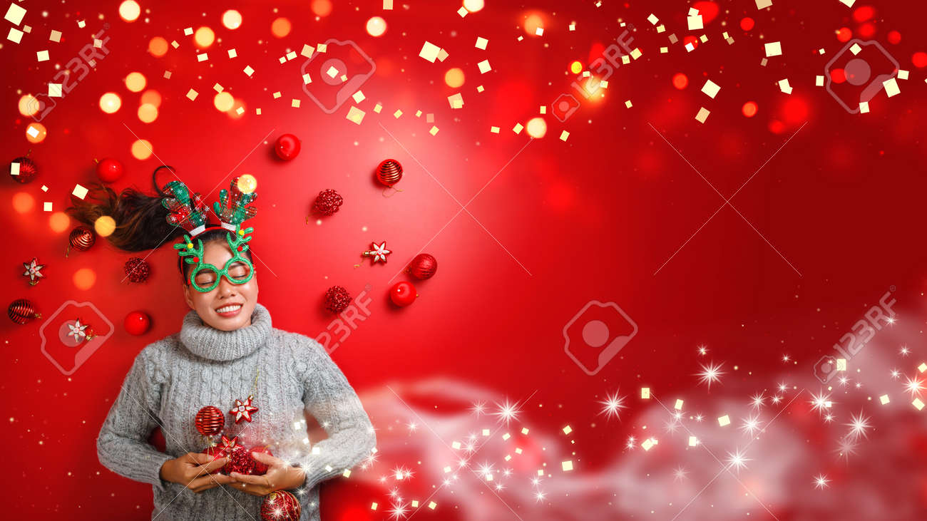 Christmas New Year. Young Woman dressed in warm sweater with Props ball red with christmas ornaments in Holiday on shine red background. Concept merry christmas. - 160113319