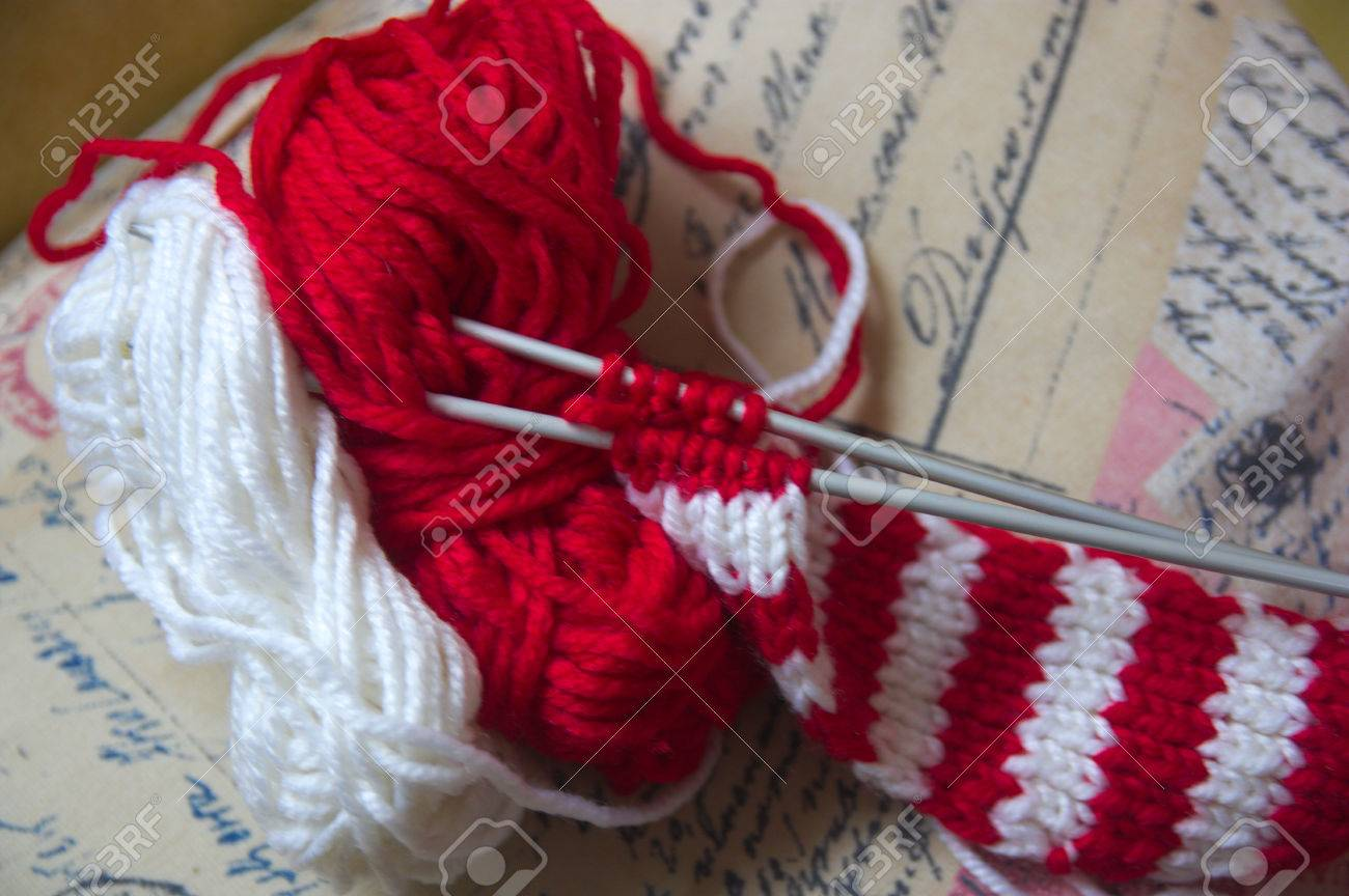 62bcdbfad0b6 Banque d images - Skeins de laine et aiguilles à tricoter pour faire une  écharpe en tissu rouge et blanc avec un fond doré