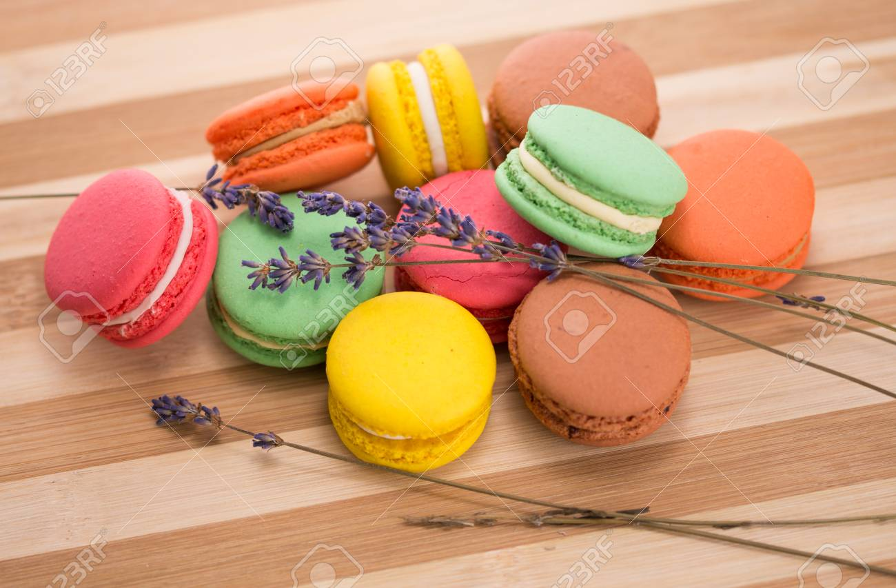 Colored Macaroons and lavender on a wooden plate