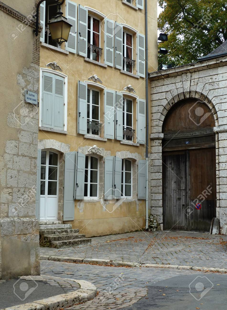 Typical French Home With Shuttered Windows And Cobblestone Streets