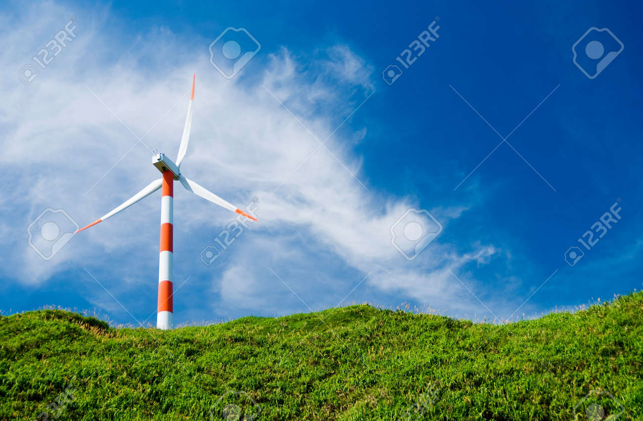 clean energy concept.  wind turbine in green hill under cloudy blue sky. Stock Photo - 7723025