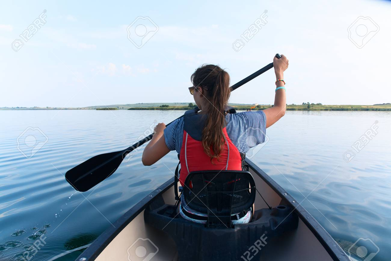f4d023b3f6 Stock Photo - Young lady with long straight brunette hair in sunglasses and  life vest paddling the kayak