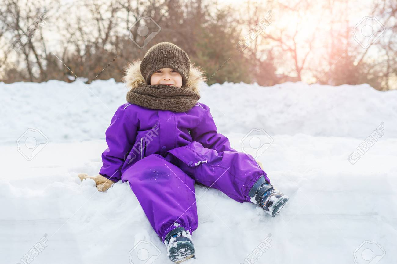 f1e139fa5 The Boy Is Sitting On A Snowbank In A Winter Overall. Warm Clothing ...