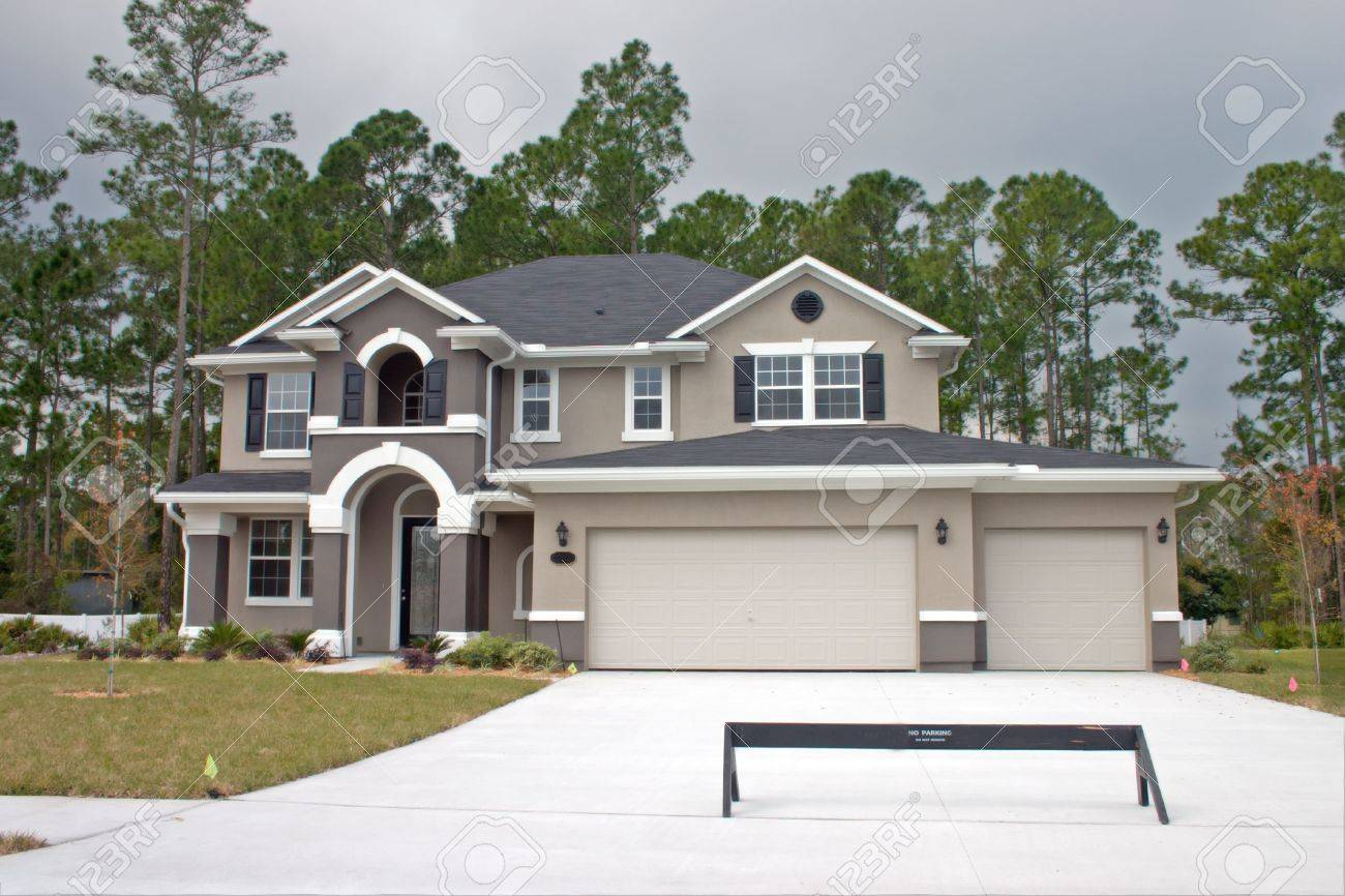 newly constructed luxury home with three car garage stock photo