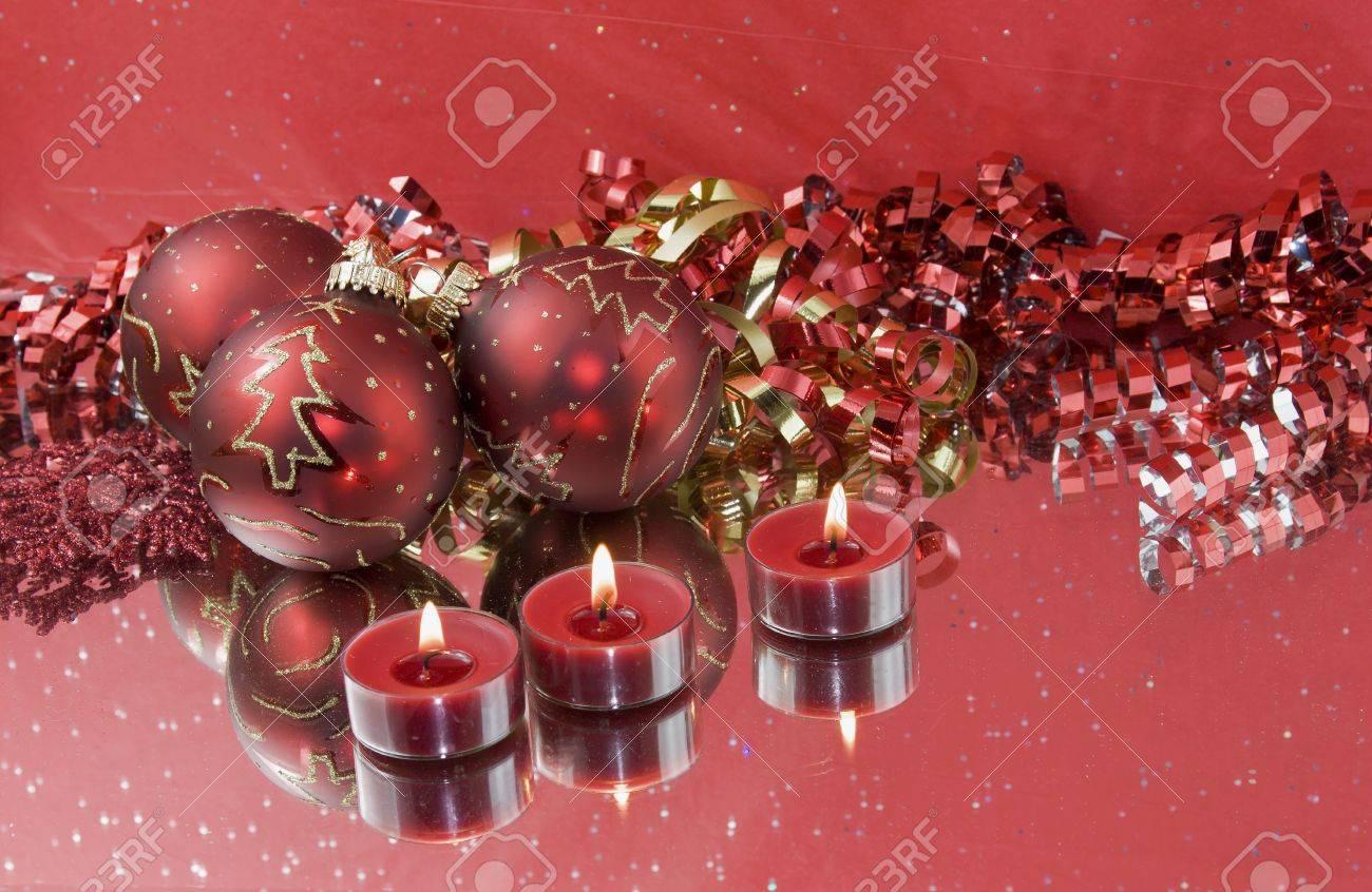 foto de archivo tres adornos navideos con velas de color rojo tealight y cinta rizado con reflexiones