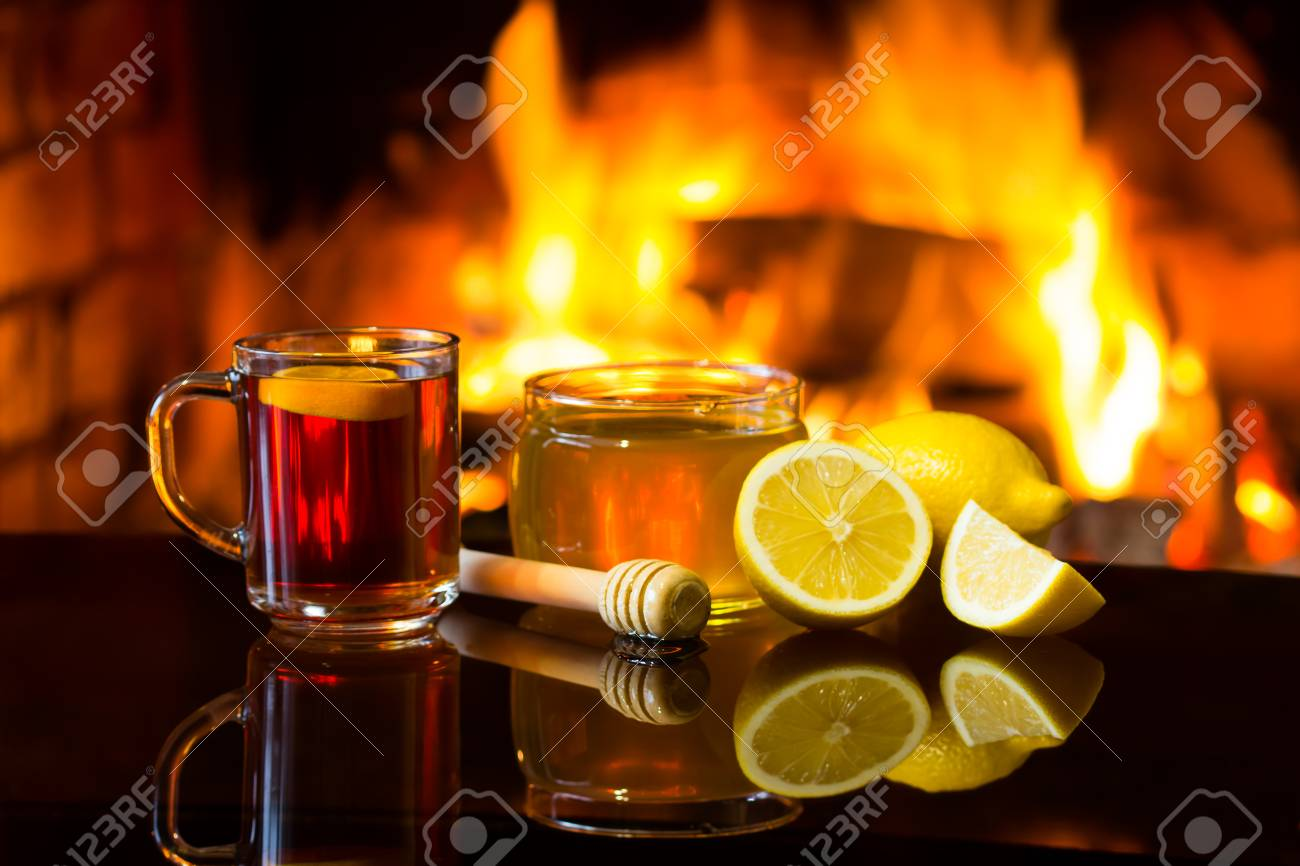Cup of hot drink wine, bowl of honey and lemon in front of warm fireplace. Magical relaxed cozy atmosphere near fire. - 57496600