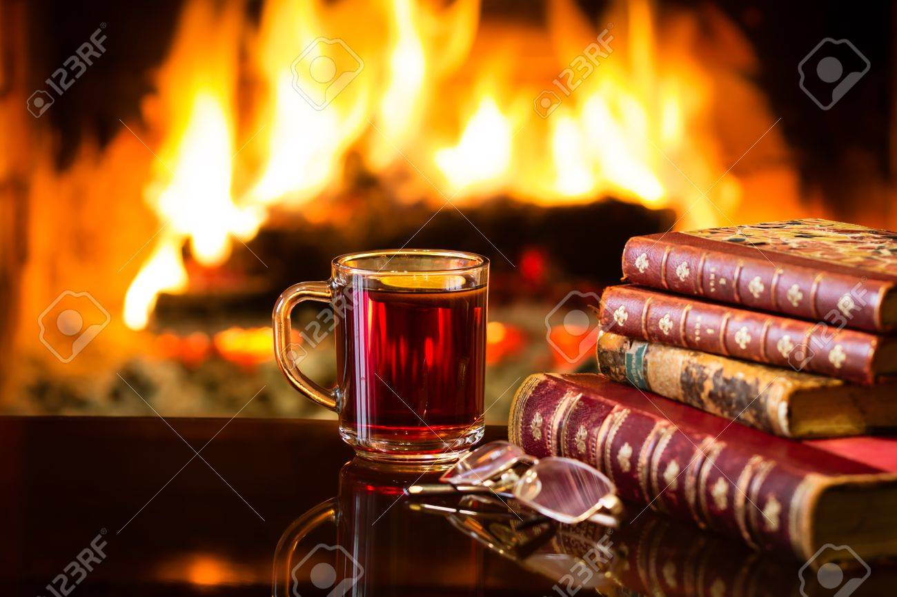 Glass mug of hot drink or alcoholic drink or mulled red wine and antique books in front of warm fireplace. Magical relaxed cozy atmosphere near fire. Autumn or winter concept - 65537228