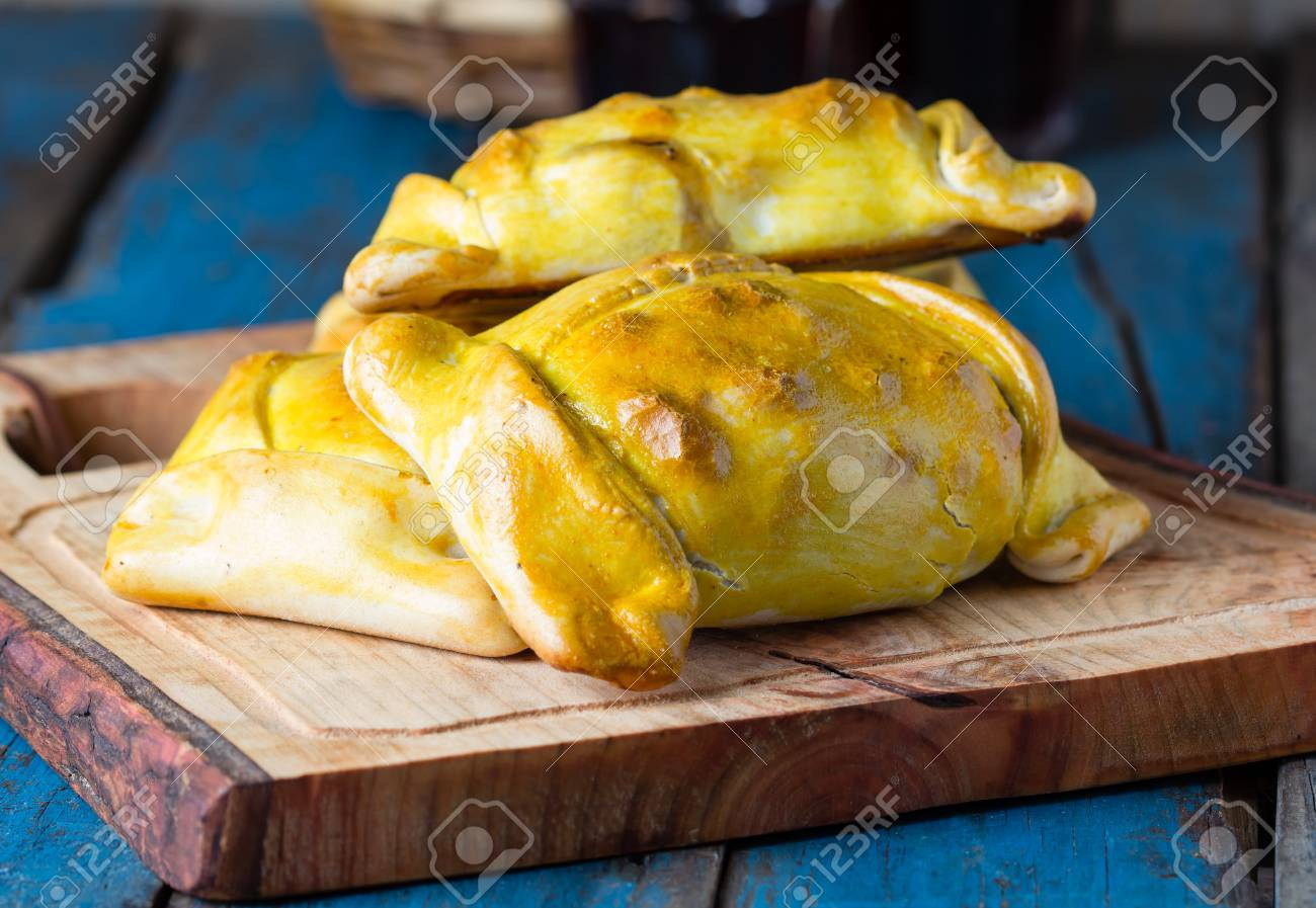 Empanadas. Latin American chilean food. Typical traditional Chilean empanadas with meat, onion, eggs and olives on mapuche rustic cutting board on wooden blue background - 65537918