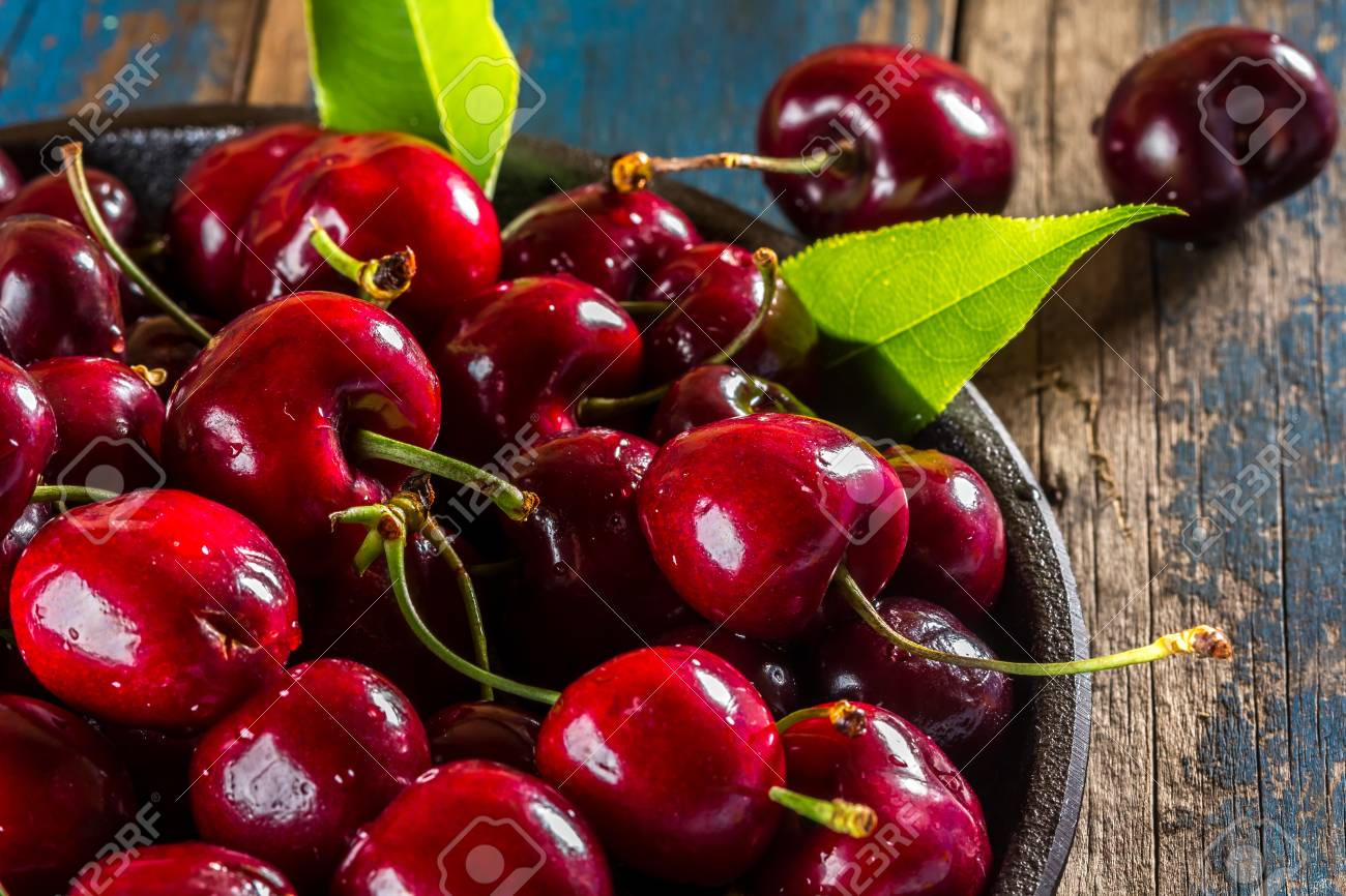Fresh cherry on black plate on wooden background. Close up - 66278458