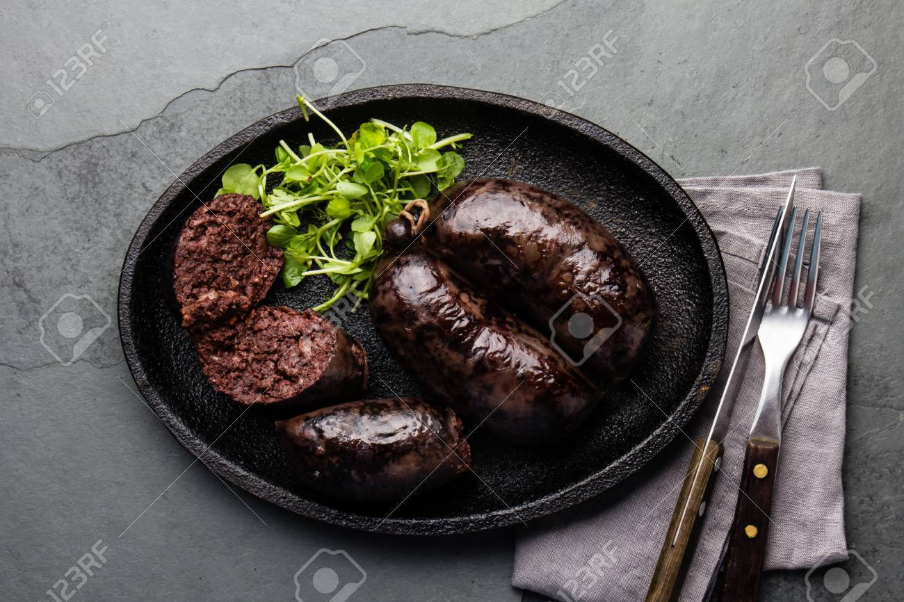 Bloody sausages - chilean preta on black iron plate, top view, grey slate background - 81366068