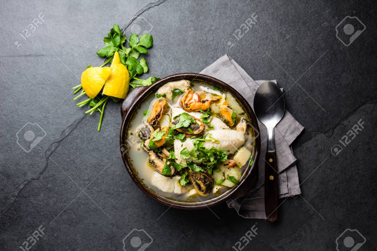 Seafood fish soup in clay bowls served with lemon and coriander. Top view, copy space. - 82504494