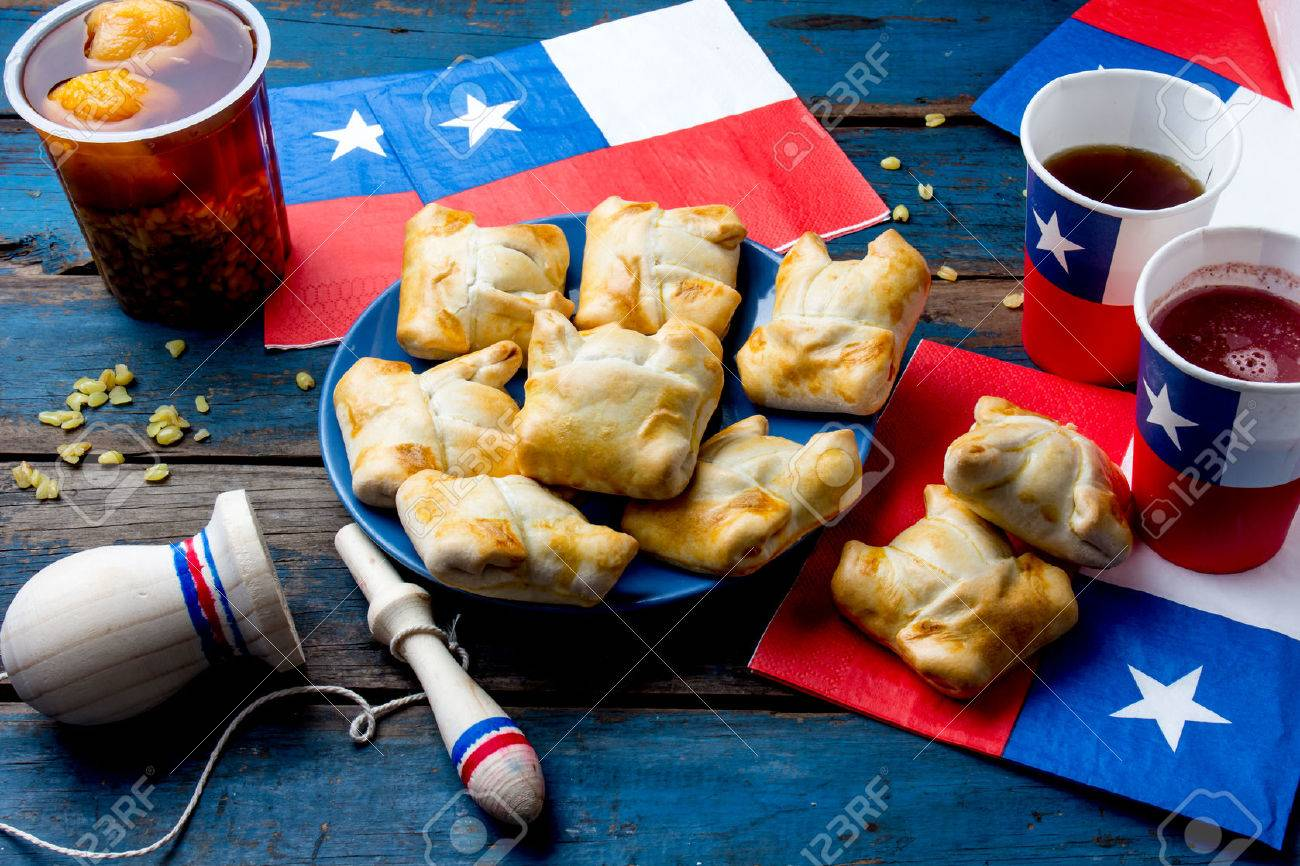 Chilean independence day concept. fiestas patrias. Chilean typical dish and drink on independence day party, 18 september. Mini empanadas, mote con huesillo, wine with toasted flour, chicha and tipical play emboque - 84704058