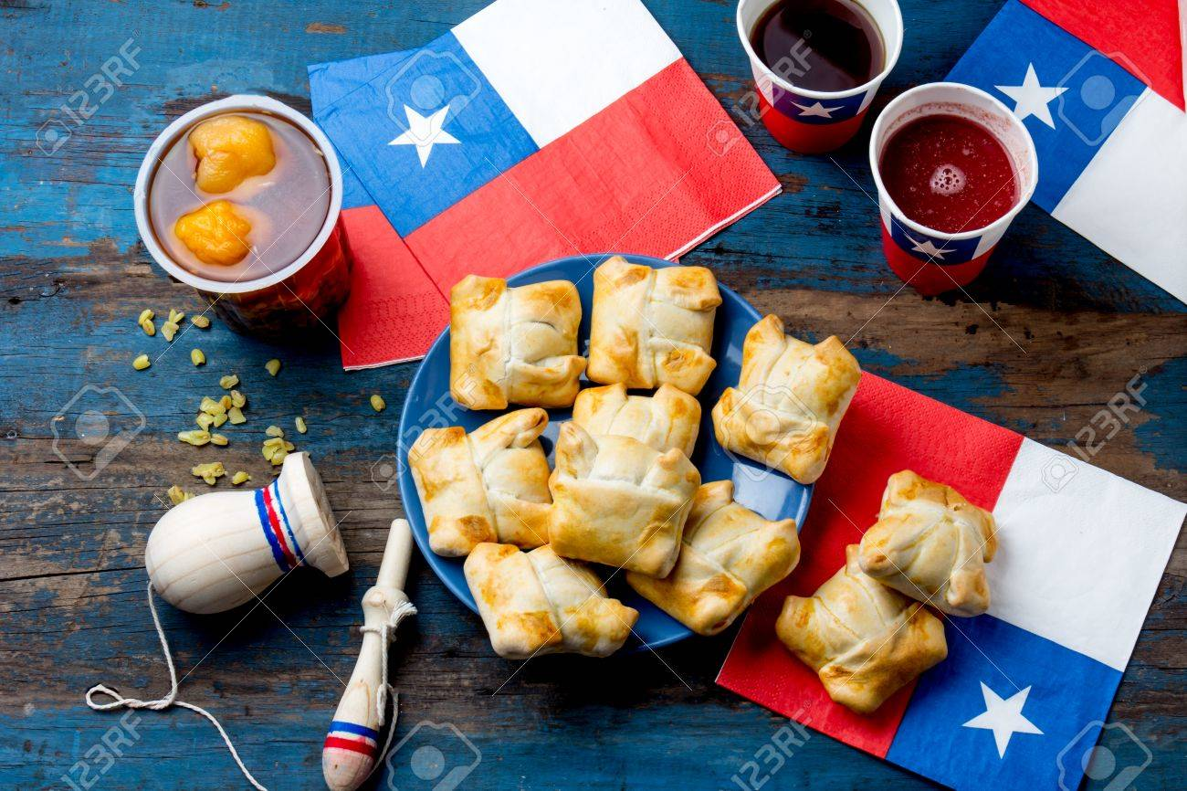 Chilean independence day concept. fiestas patrias. Chilean typical dish and drink on independence day party, 18 september. Mini empanadas, mote con huesillo, wine with toasted flour, chicha and tipical play emboque - 84704062
