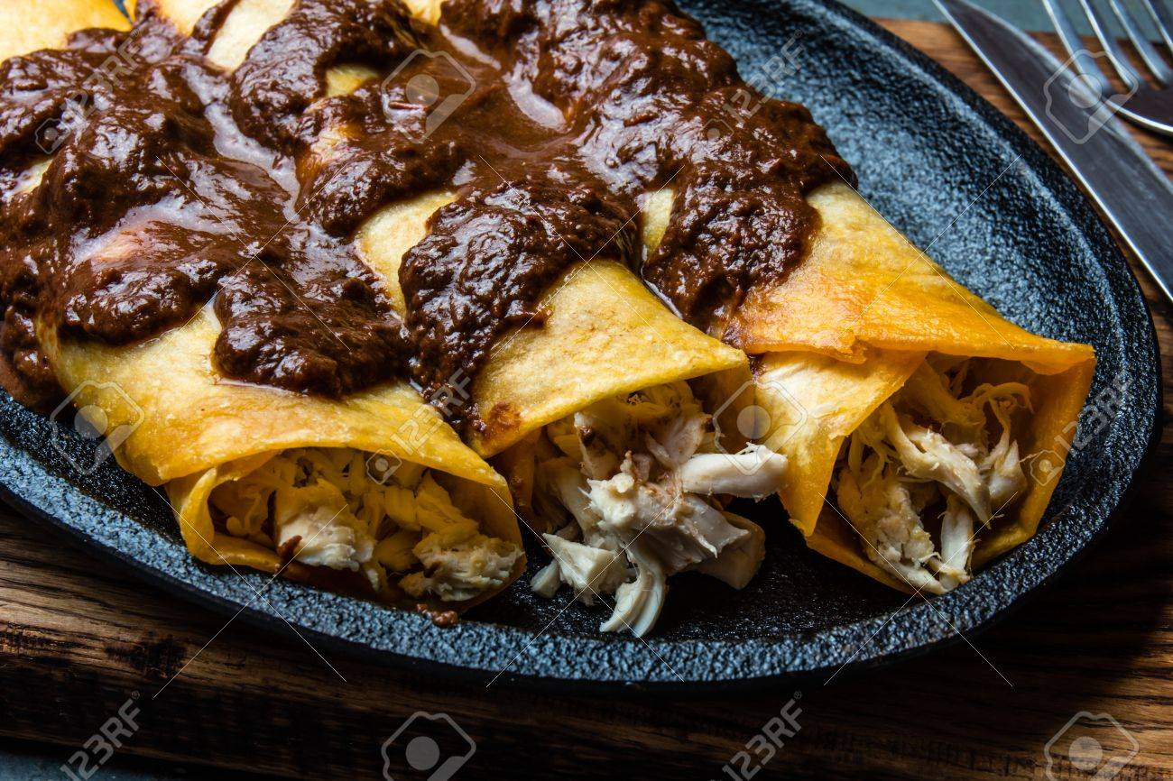 Mexican cuisine. Traditional Mexican chicken enchiladas with spicy chocolate salsa mole poblano. Enchiladas with sauce moole from Puebla, Mexico - 84705840