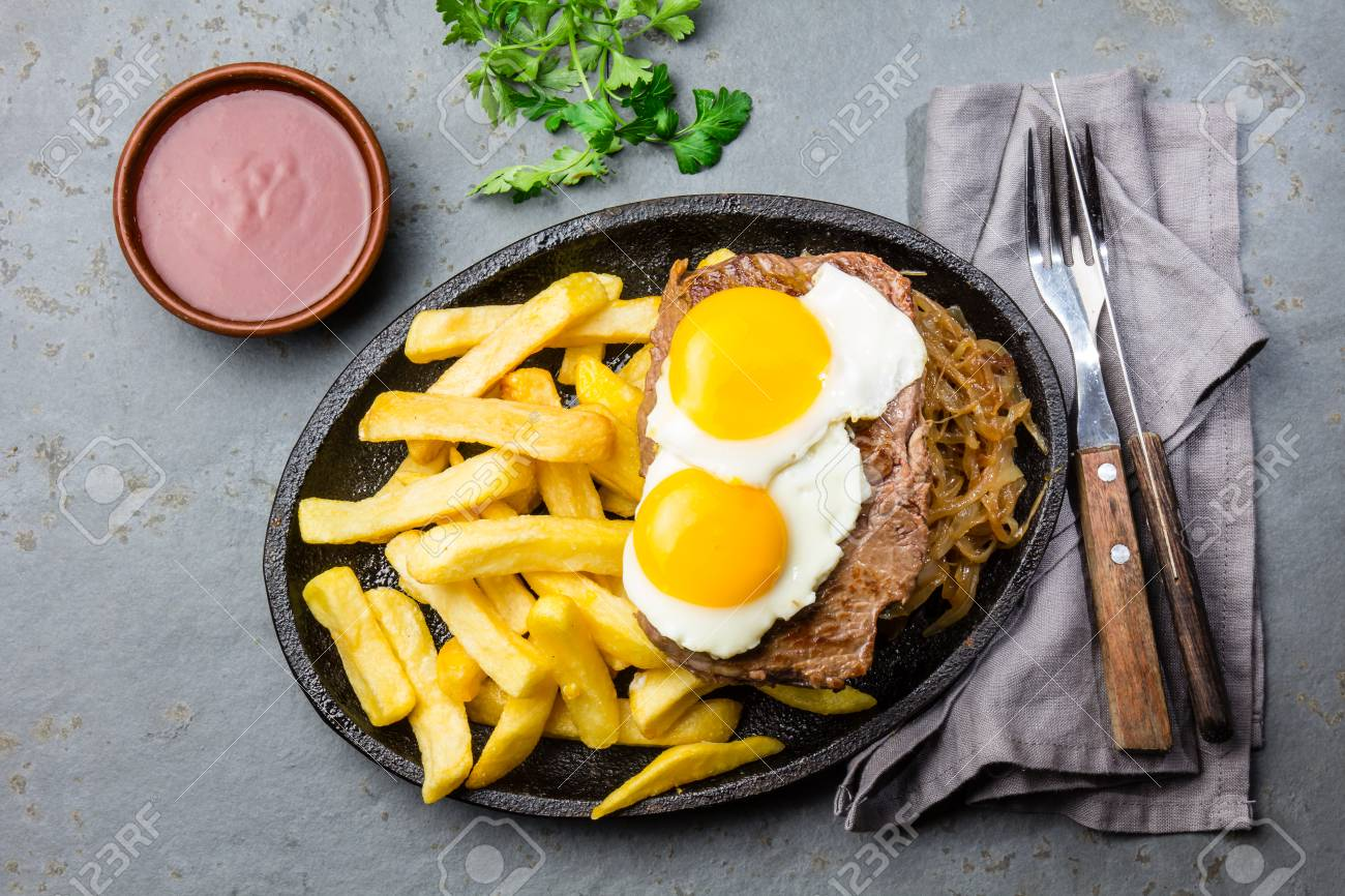 Peruvian Latin American food. Lomo a lo pobre. Beef tenderloin whit fried potatoes french fries and eggs - 84705848