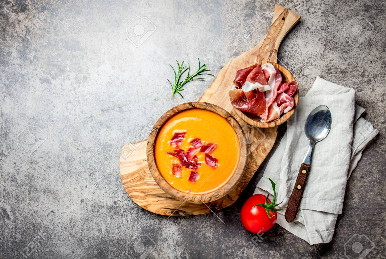Spanish tomato soup Salmorejo served in olive wooden bowl with ham jamon serrano on stone background. Top view, copy space. - 87950686
