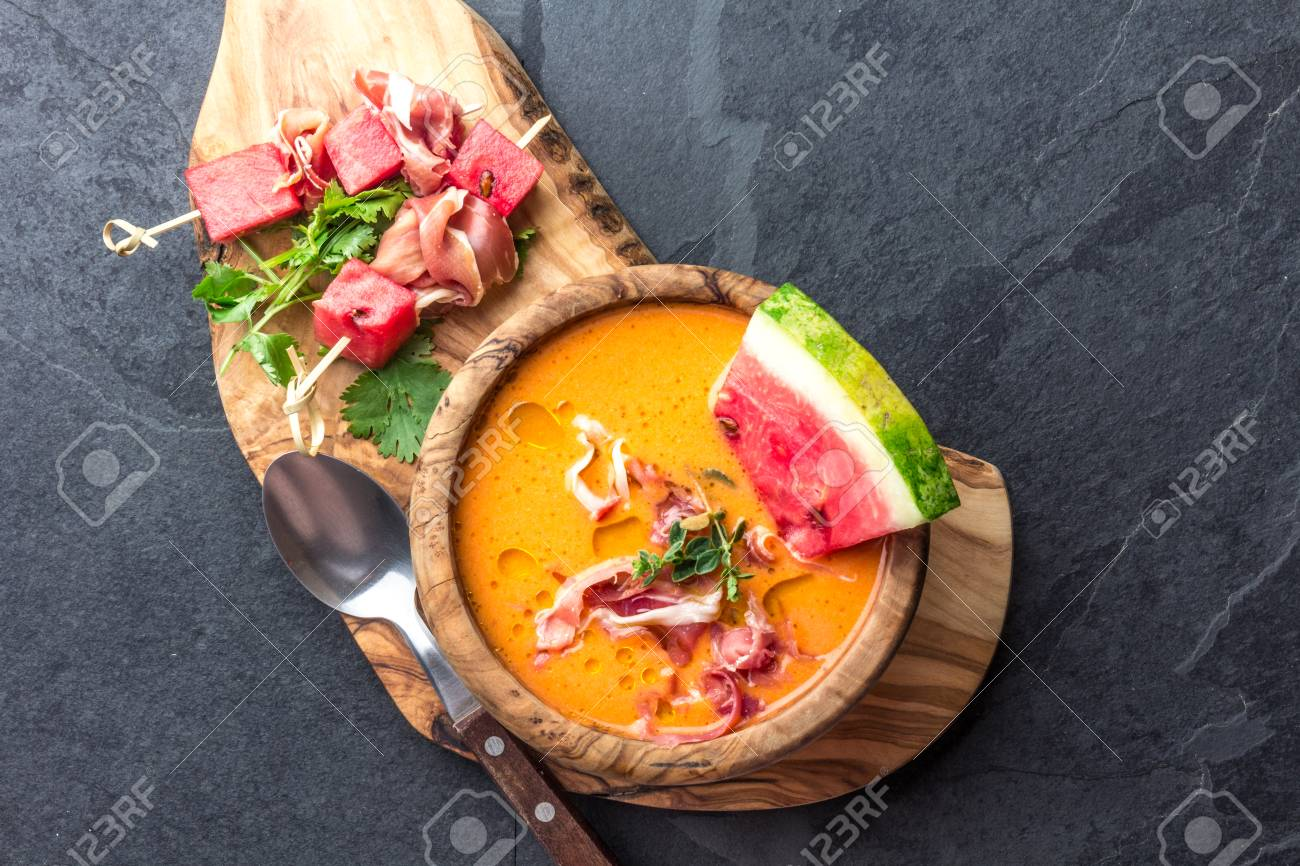 Salmorejo soup with watermelon. Traditional spanish cold tomato soup with watermelon and ham serrano in olive wooden bowl, slate background, top view - 91335924