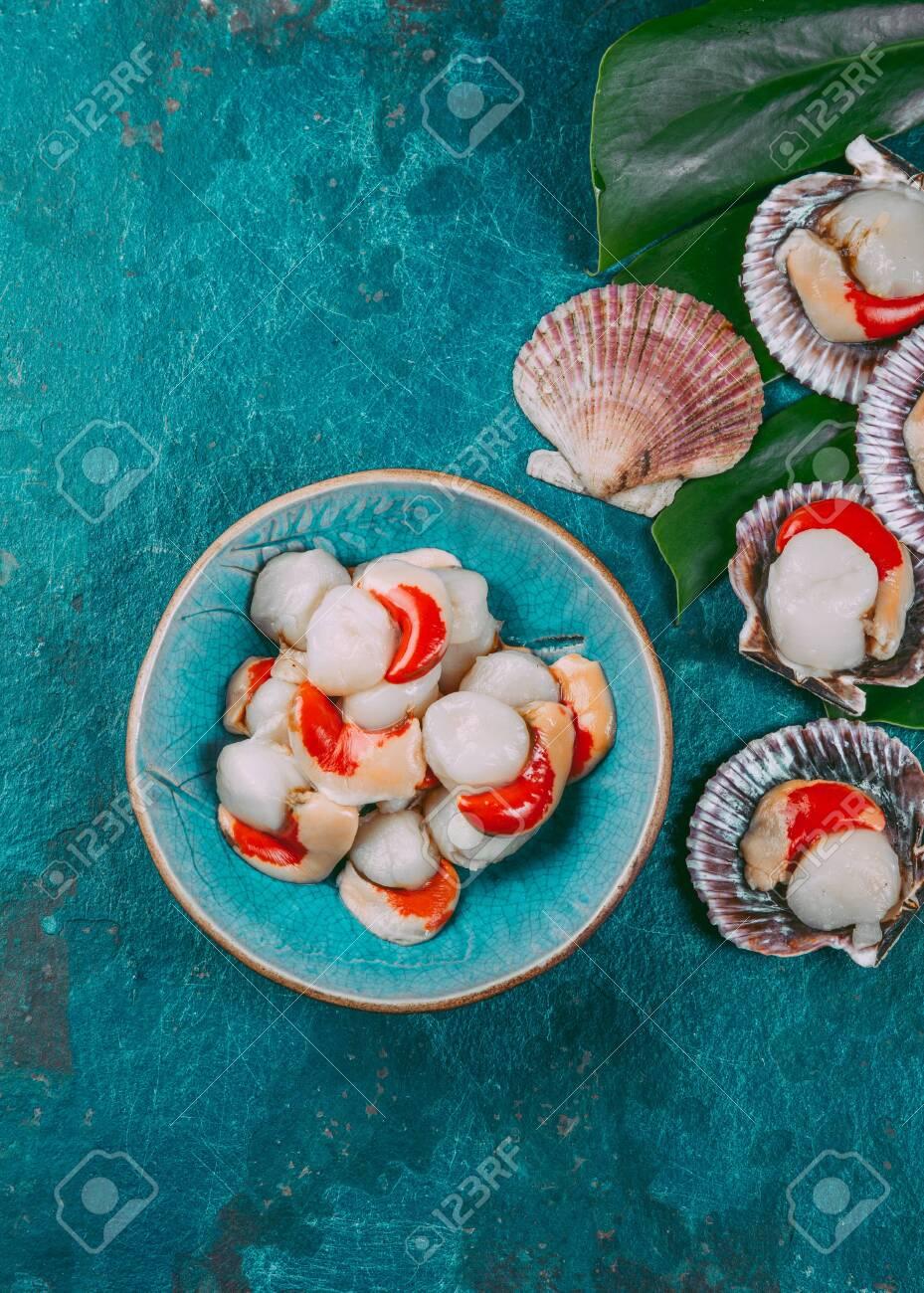 Raw fresh seafood shellfish scallops on blue background. - 130165459