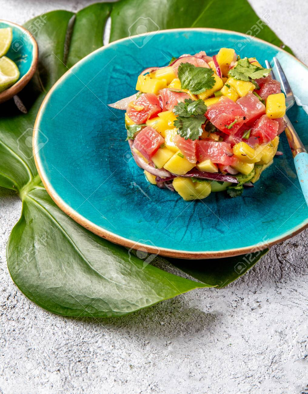 Tropical style gourmet tuna mango salad tartar with cilantro and purple onion. On blue plate, tropical leaves. - 130165627