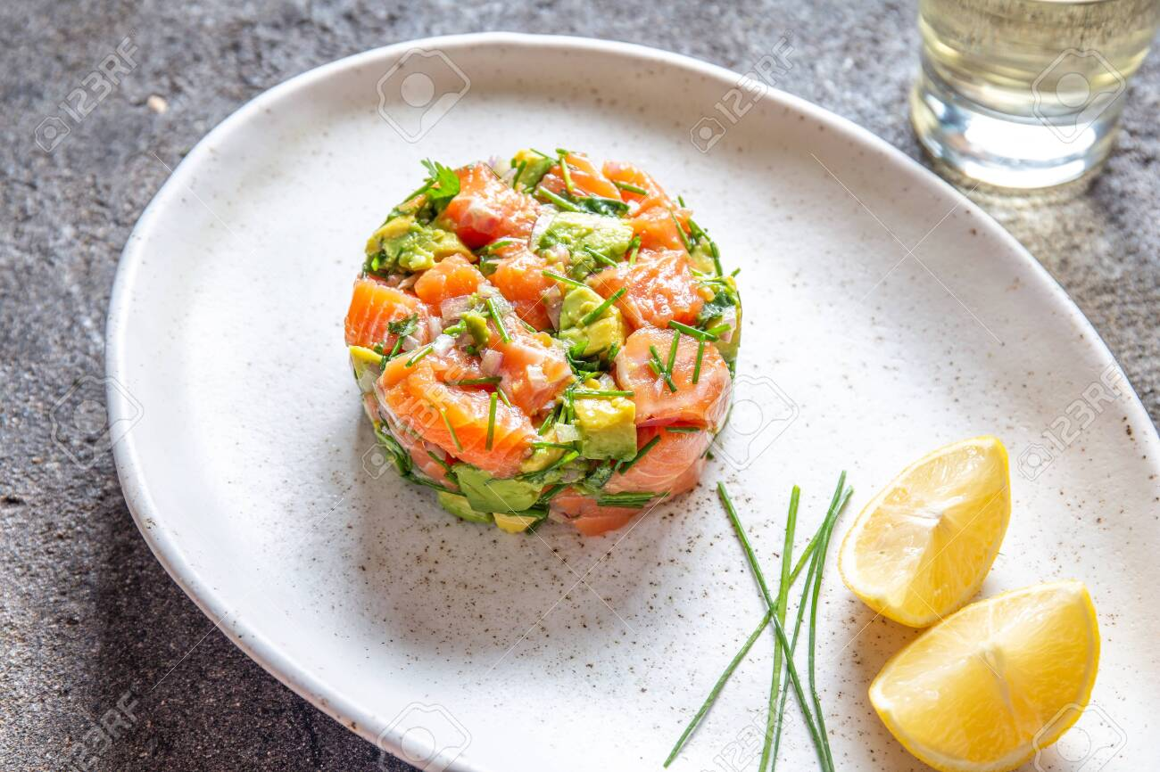 PERUVIAN FOOD. Salmon ceviche with avocado, spring onion and lemon on white plate served with white wine. - 133655131