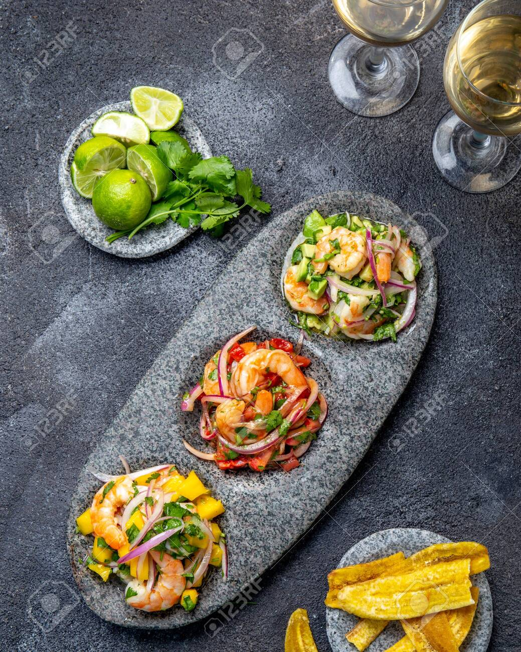CEVICHE. Three colorful shrimps ceviche with mango, avocado and tomatoes. Latin American Mexican Peruvian Ecuadorian food. Served with white wine and banana chips - 137085277