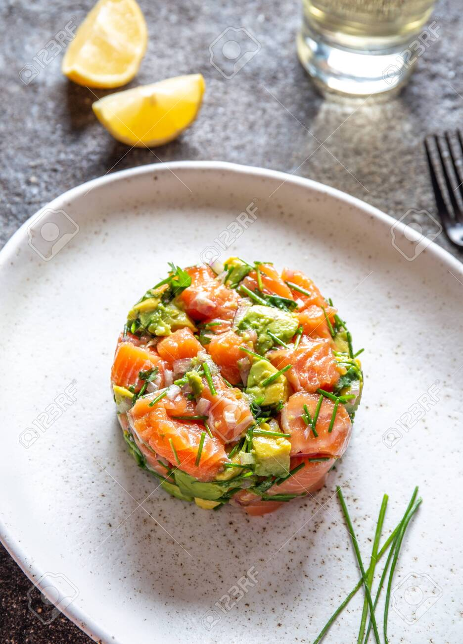 PERUVIAN FOOD. Salmon ceviche with avocado, spring onion and lemon on white plate served with white wine. - 138530701