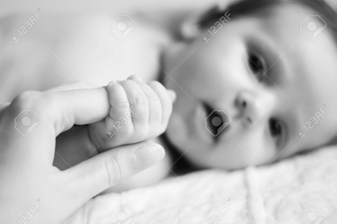 A baby holding a finger of his parents Stock Photo - 7625522