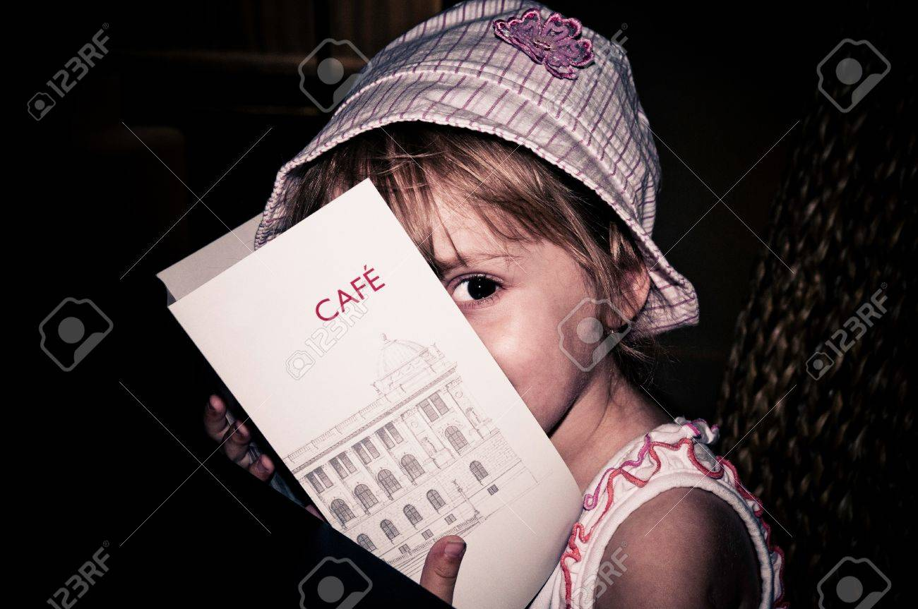 Little girl sitting in a cafe and reading the menu Stock Photo - 10180666