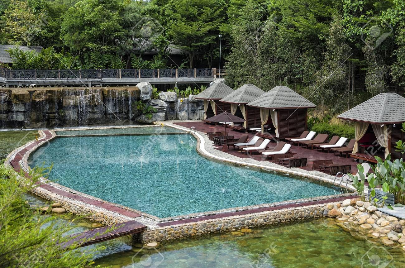 Beautiful Swimming Pool, Chair and Hut in tropical resort - relaz..