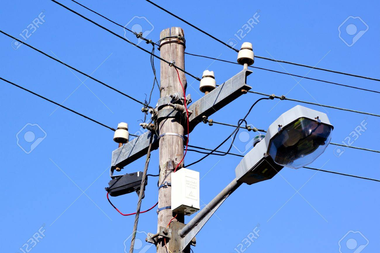 A wooden streetlight pole with a lamp connected with cables and a wooden streetlight pole with a lamp connected with cables and red wires on an isolated arubaitofo Choice Image