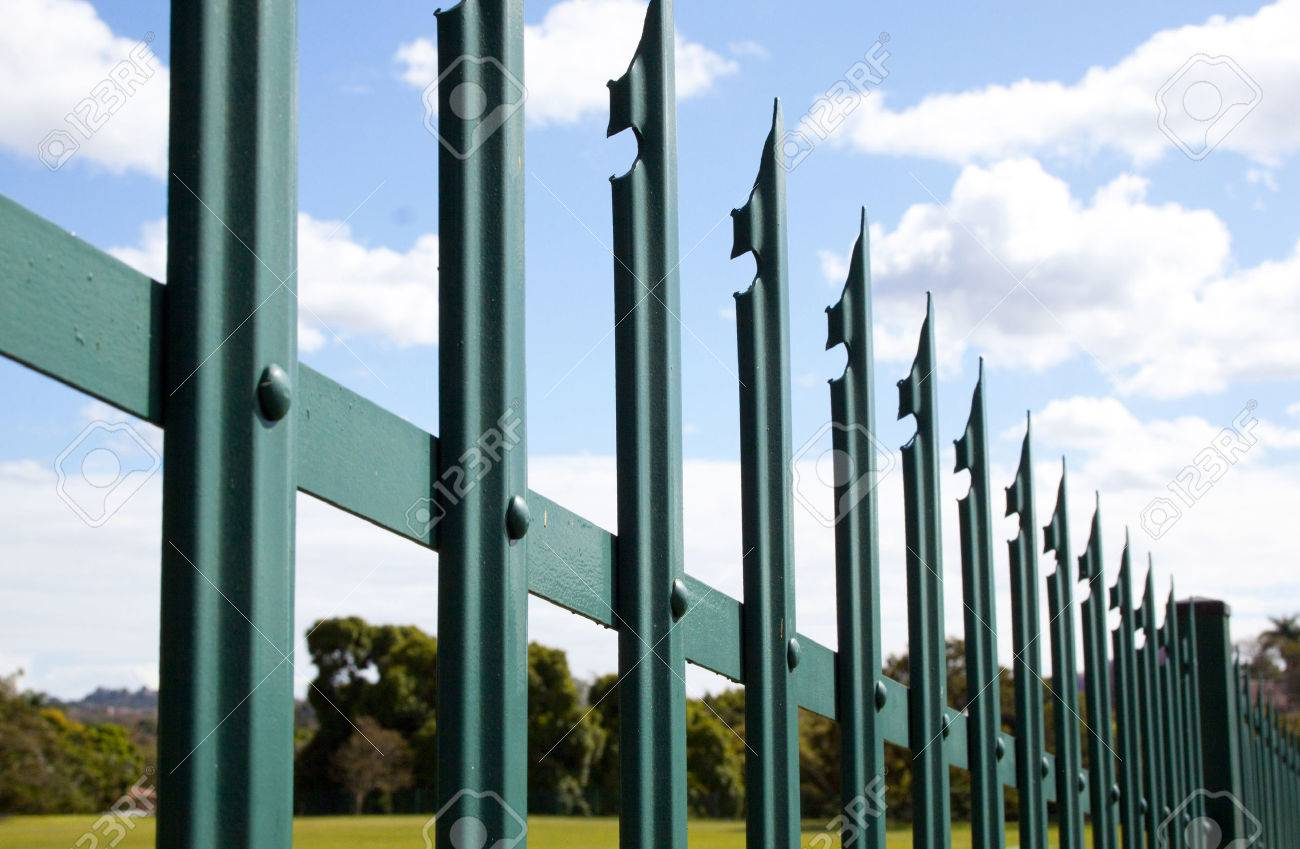 security fence closeup of green steel palisade security fence against blue sky and clouds