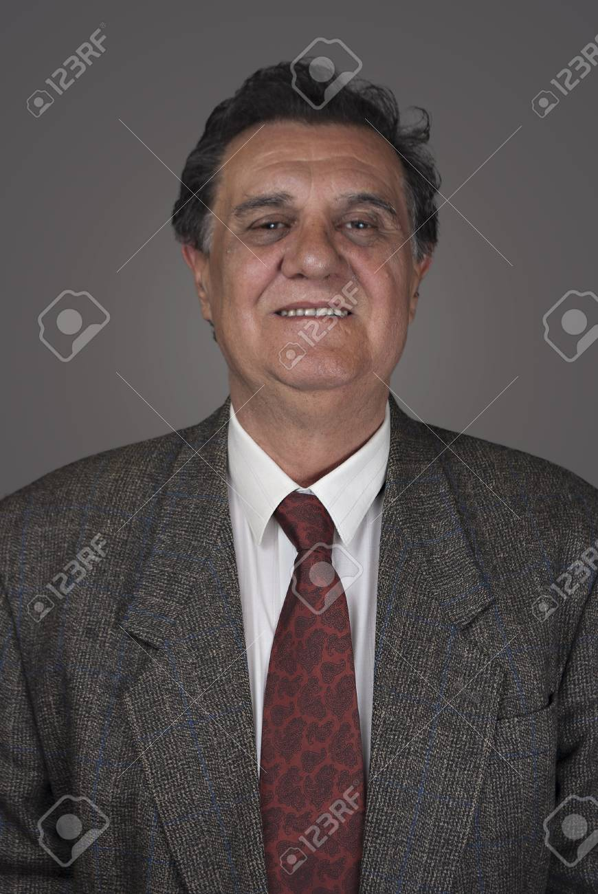 Tired businessman standing against gray background Stock Photo - 9354028