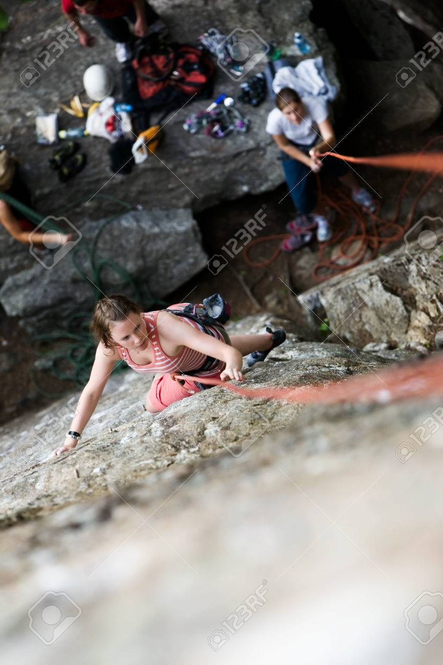 A female climber on a steep rock face viewed from above with the belayer in the background.  Shallow depth of field is used to isolated the climber. Stock Photo - 1543428