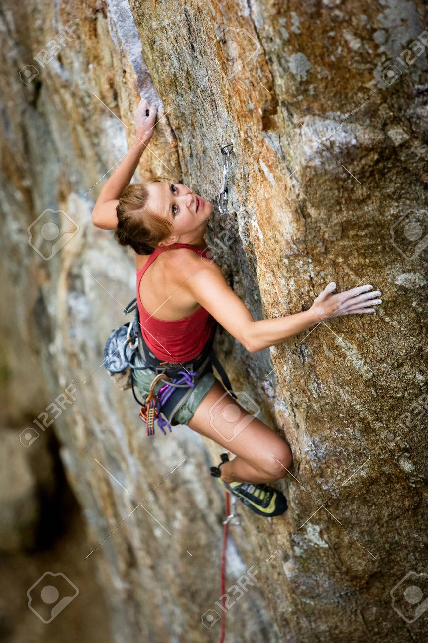 An eager female climber on a steep rock face looks for the next hold - viewed from above.  Shallow depth of field is used to isolated the climber. Stock Photo - 1543485