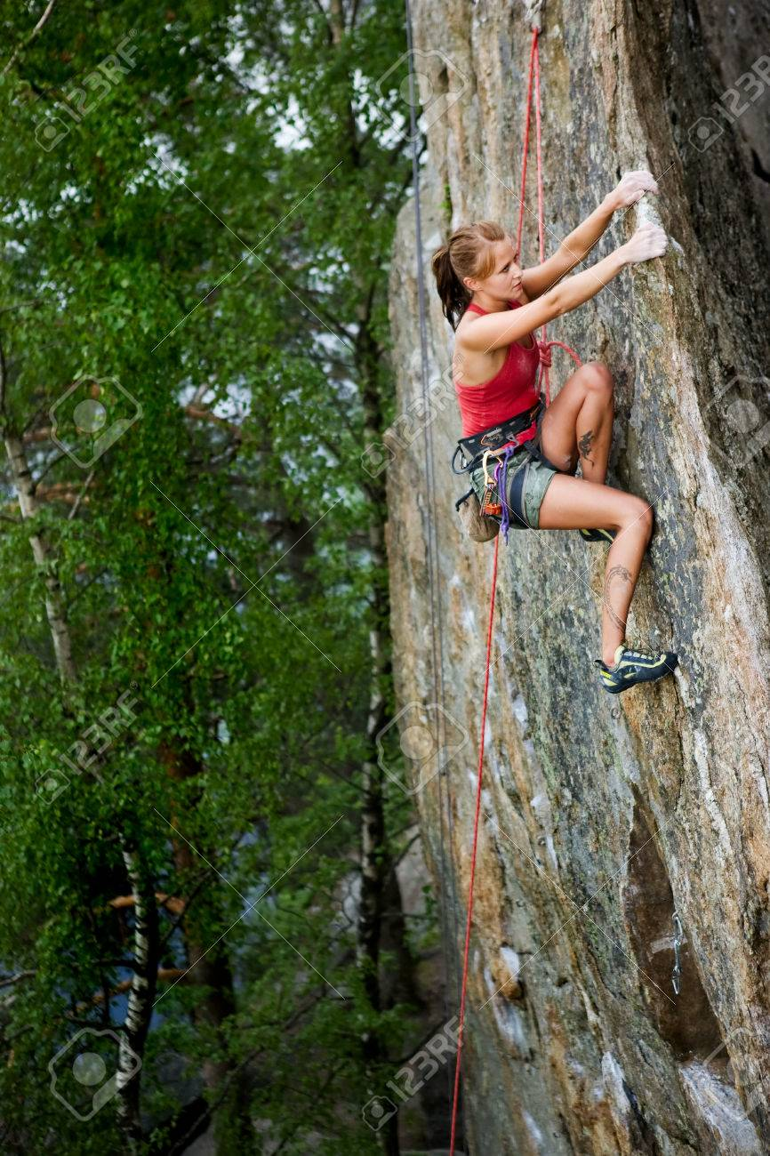 An eager female climber on a steep rock face looks for the next hold. Shallow depth of field is used to isolated the climber with the focus on the head. Stock Photo - 1543490
