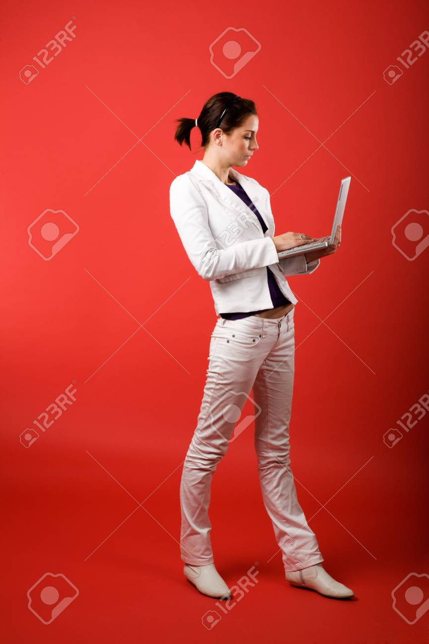 A young woman typing on a laptop computer isolated on red Stock Photo - 2346311