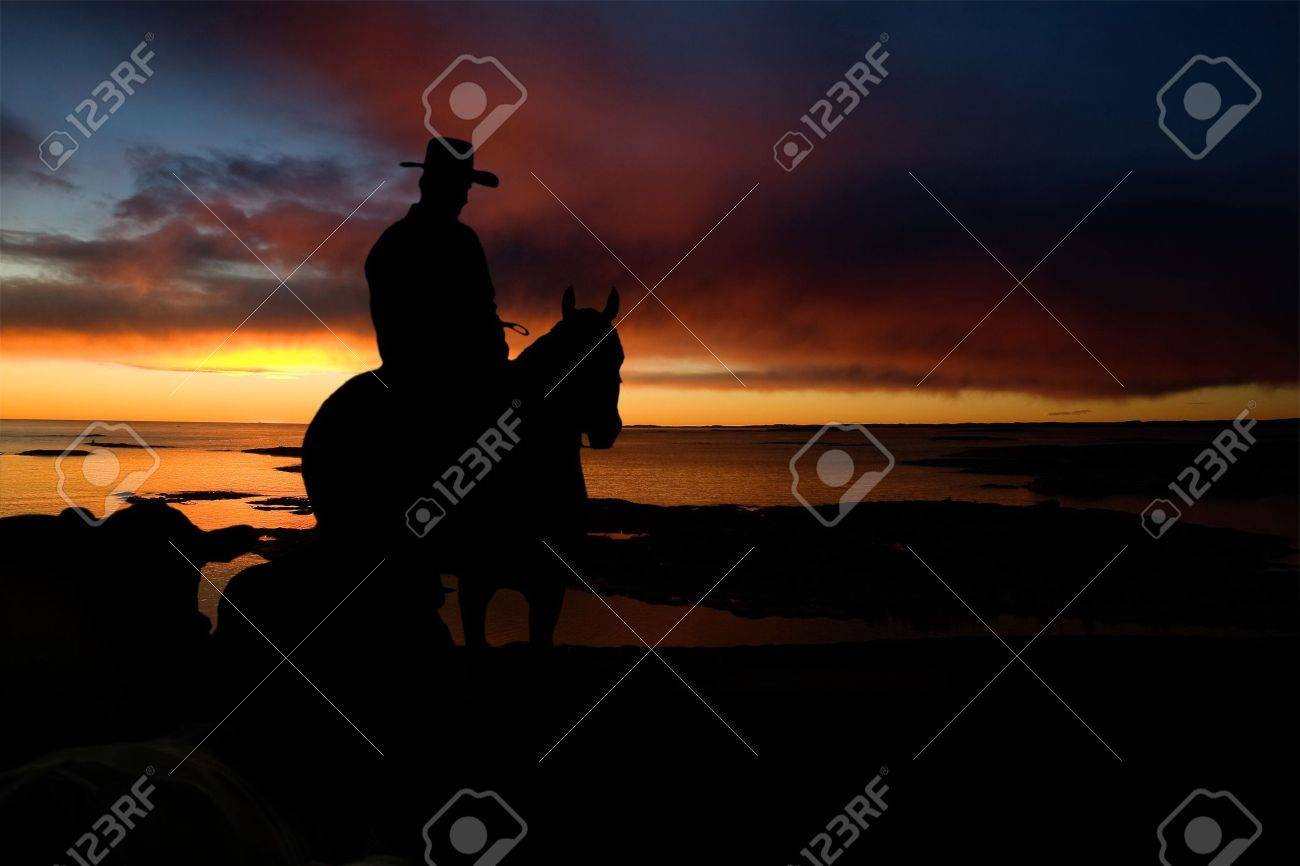 A cowboy on a hill against a sunset and ocean Stock Photo - 2947942