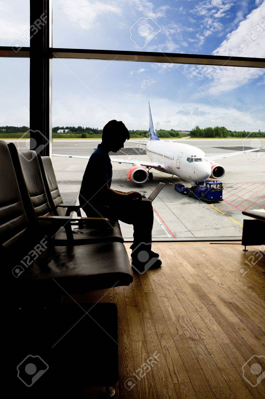 A young man using a laptop in an airport terminal Stock Photo - 3418699