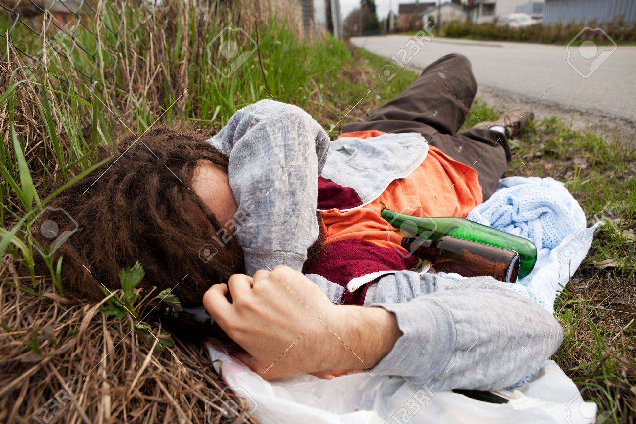 A homeless drunk person laying by the edge of the road Stock Photo - 5693536