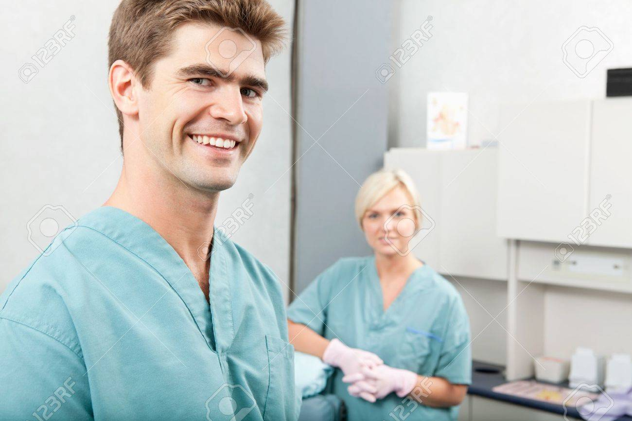 Portrait Of Male Dentist With Female Assistant Standing At Dental ...
