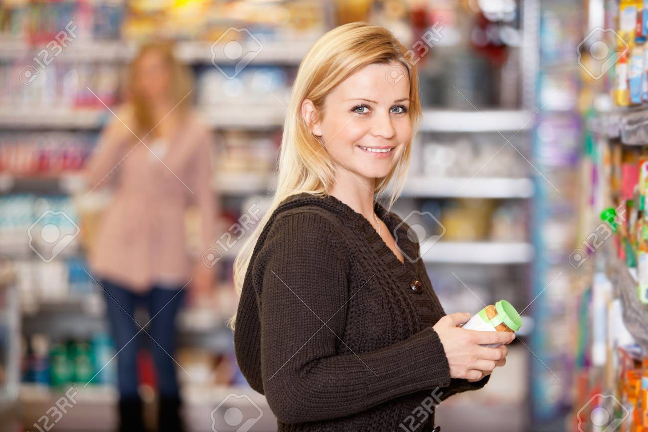 Portrait of a young woman smiling while shopping in the supermarket Stock Photo - 9470807