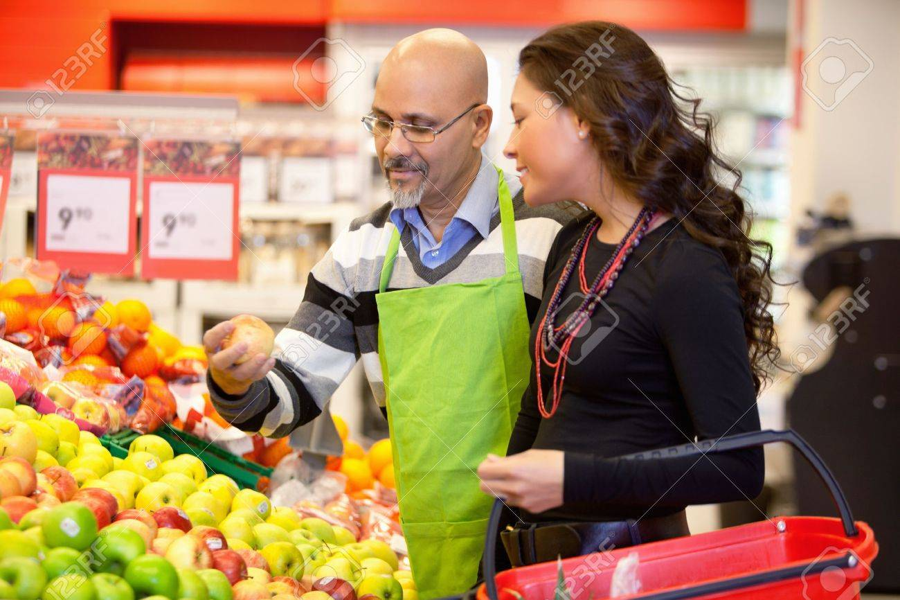 Shop assistant holding apple with customer in the supermarket Stock Photo - 9470710