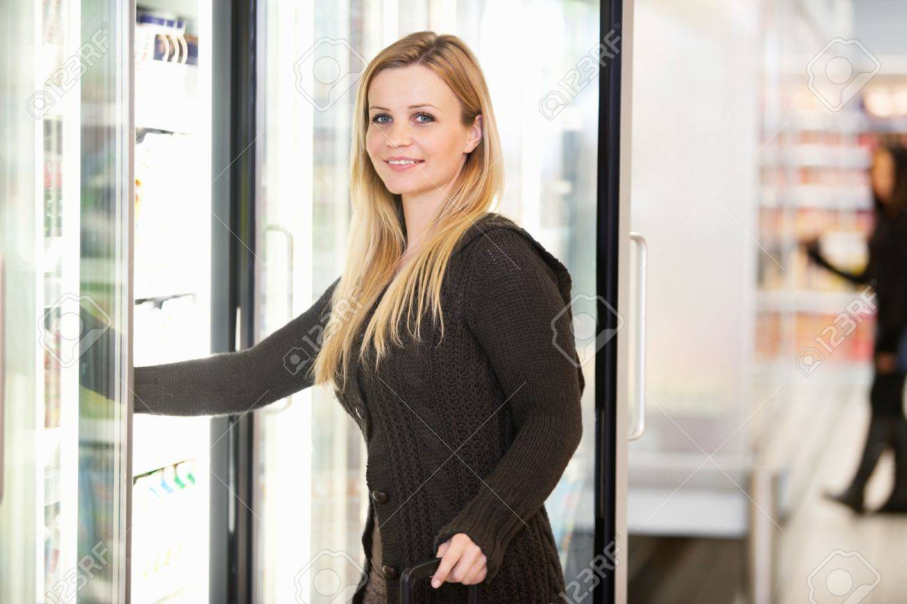 Smiling woman in front of refrigerator looking at camera with person in the background Stock Photo - 9470551