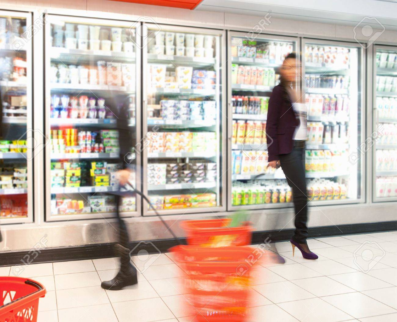 Blurred motion of people walking near refrigerator in shopping centre with baskets Stock Photo - 9470644