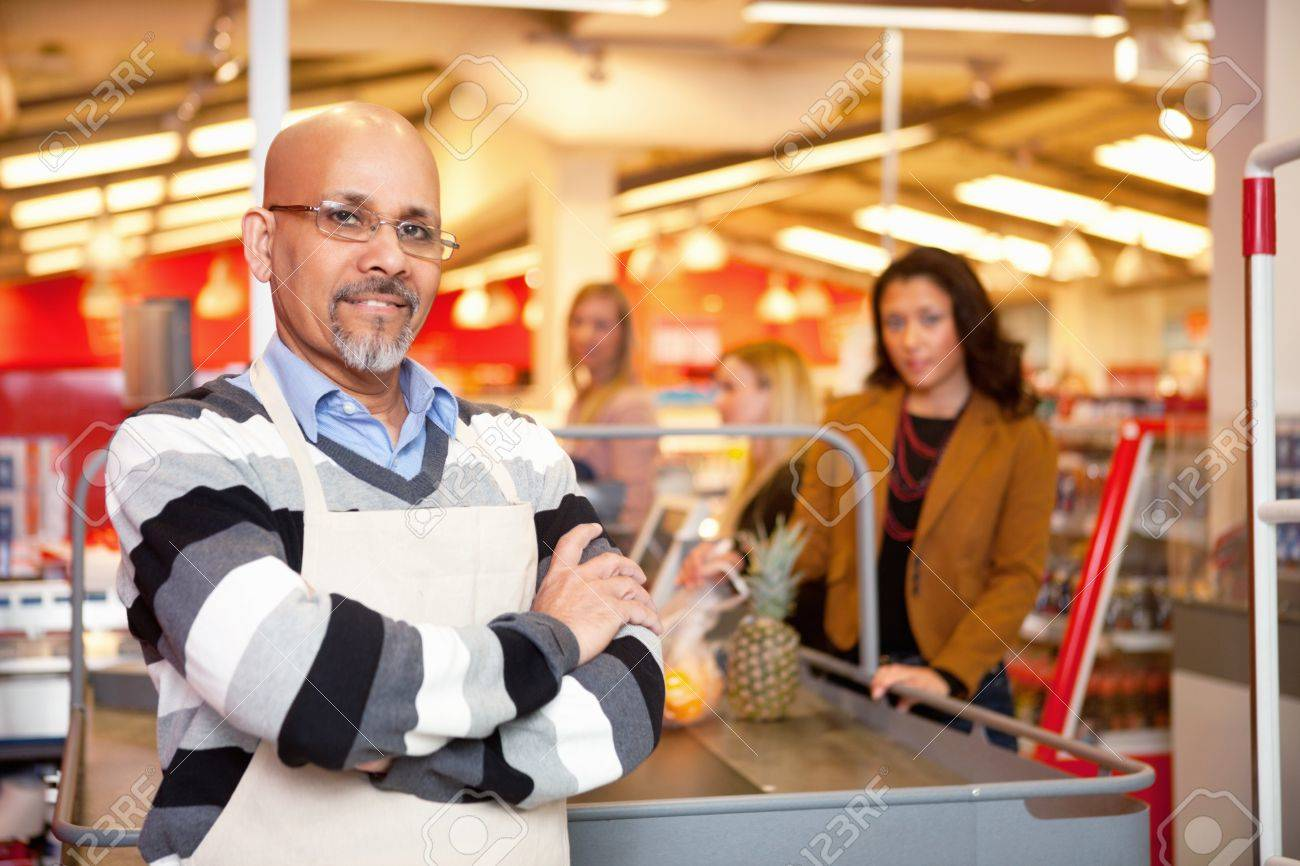 Portrait of a grocery store cashier standing at a checkout counter Stock Photo - 9600018